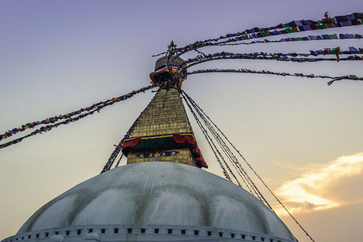 Boudhanath Stupa World Heritage Site By UNESCO Architecture Belief Building Exterior Built Structure Cloud - Sky Decoration Dusk Flag Low Angle View Nature No People Outdoors Place Of Worship Religion Sky Spirituality Sunset Tall - High Travel Destinations