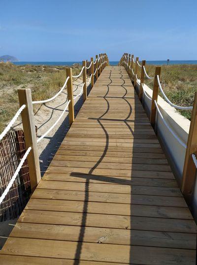 Wooden footbridge leading towards sea against sky
