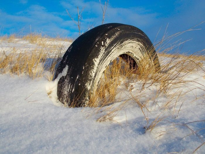 Close-up of abandoned tire in snow