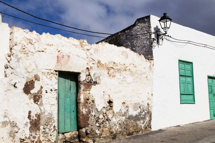 shabby house in Teguise, Lanzarote, Canary Islands Ailing Condition Architecture Building Exterior Built Structure Cable Canary Islands Day Electricity  House Lanzarote No People Outdoors Power Line  Power Supply Residential Building Shabby Sky SPAIN Street Sunlight Teguise