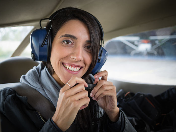 Portrait of a smiling young woman in airplane