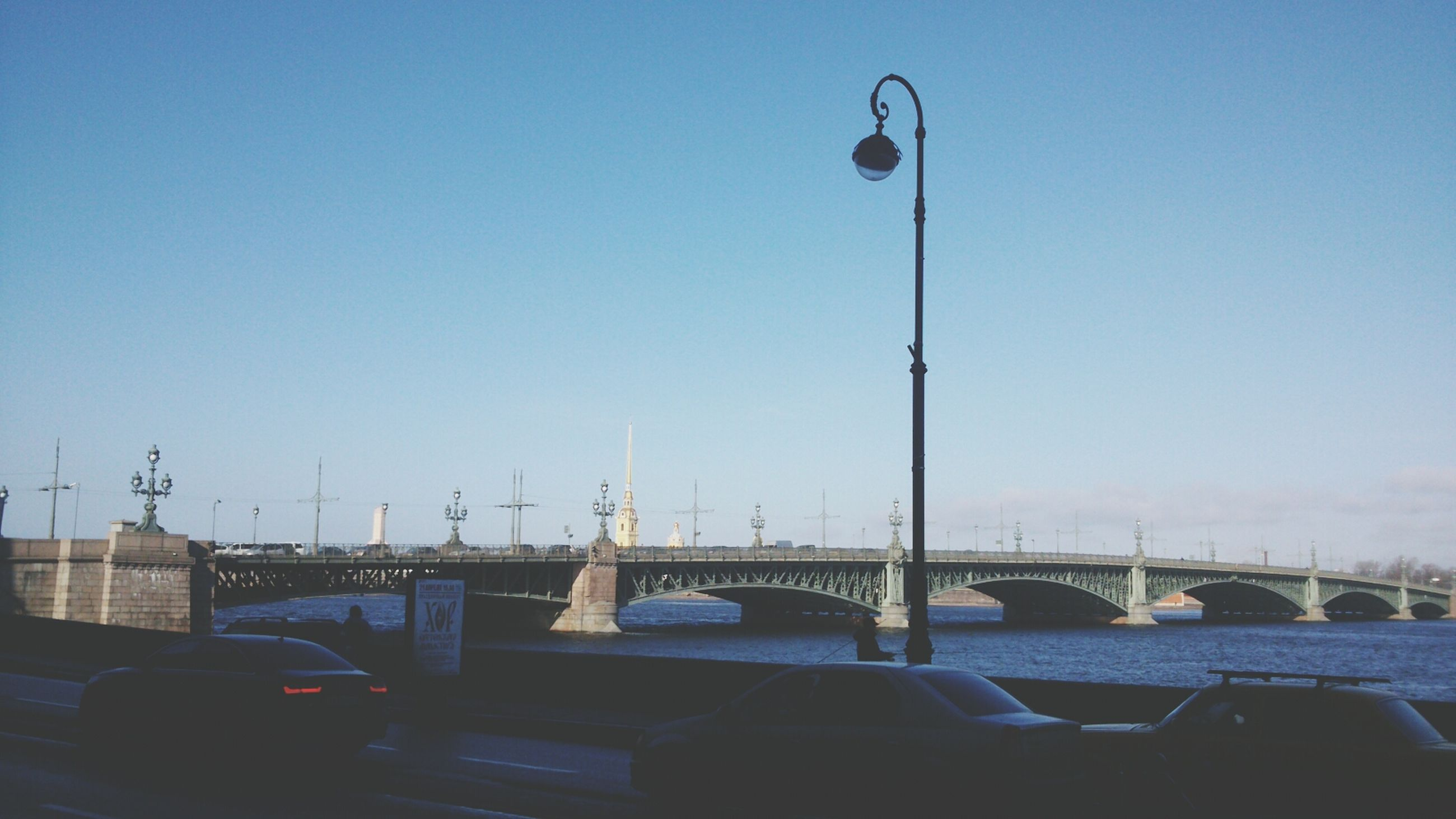 clear sky, built structure, architecture, copy space, building exterior, low angle view, street light, blue, connection, outdoors, day, railing, transportation, no people, city, lighting equipment, sky, sunlight, building, bridge - man made structure