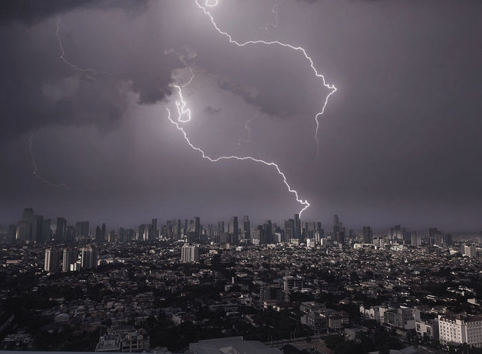 Lightning over illuminated cityscape against sky at night