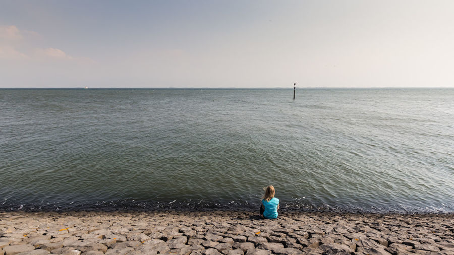 Rear view of woman sitting on beach against sky