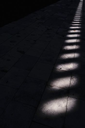 High angle view of sunlight falling on footpath