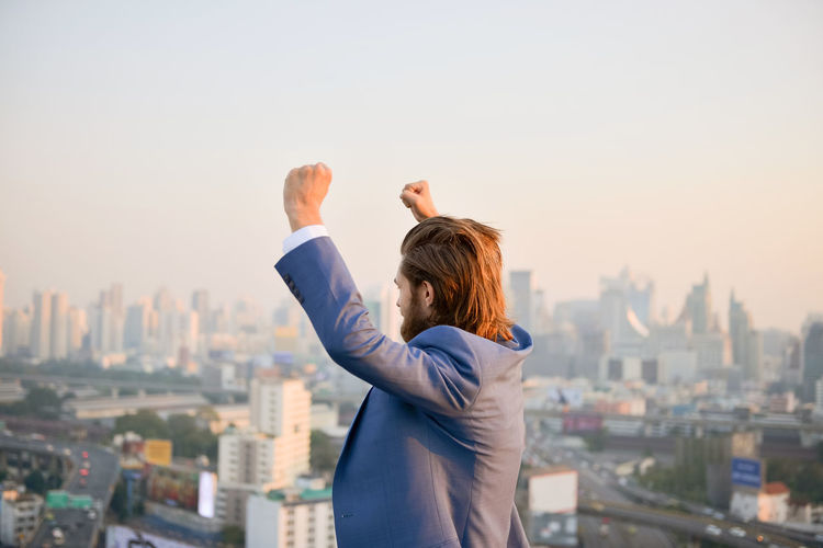 Rear view of woman standing on city against clear sky