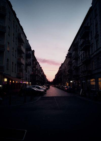 City street amidst buildings against sky at dusk