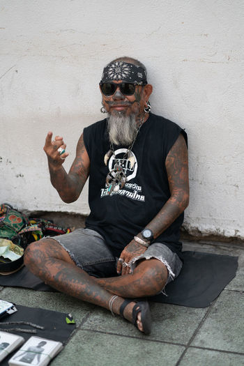 TATTOOED MAN OF BANGKOK One Person Sitting Real People Full Length Looking At Camera Front View Glasses Portrait Casual Clothing Sunglasses Gesturing Adult Beard Mature Men Tattoos Tattoed Bandana Homeless Man One Man Only Sitting Outside Sitting Elderly Artist