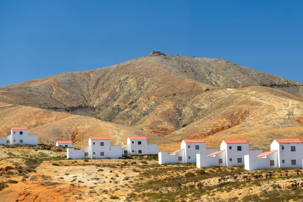 HOUSES AGAINST MOUNTAINS AGAINST CLEAR BLUE SKY