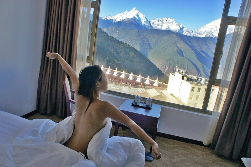 Rear View Of Topless Young Woman Relaxing On Bed In Hotel Room