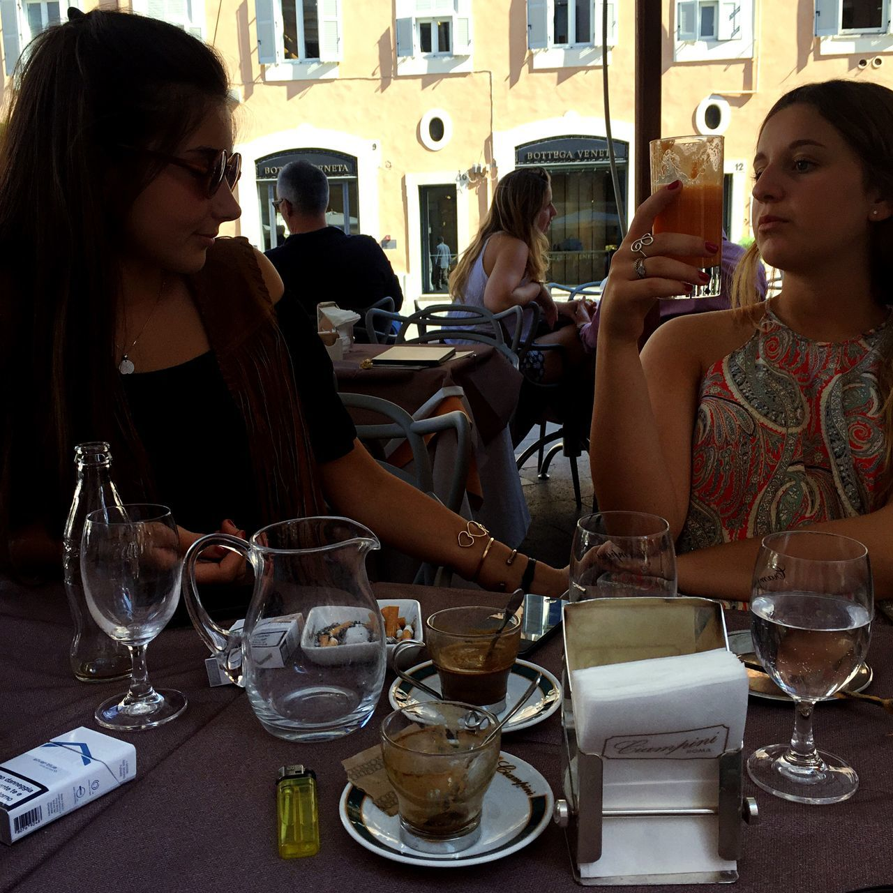 real people, wineglass, table, restaurant, two people, leisure activity, lifestyles, food and drink, women, wine, day, drink, togetherness, drinking glass, friendship, outdoors, sitting, men, building exterior, architecture, young women, young adult, adult, people