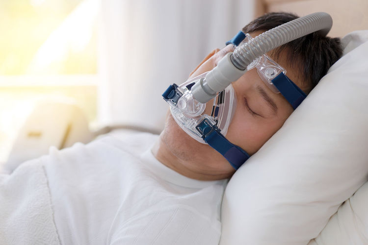 Midsection of man wearing mask in bed