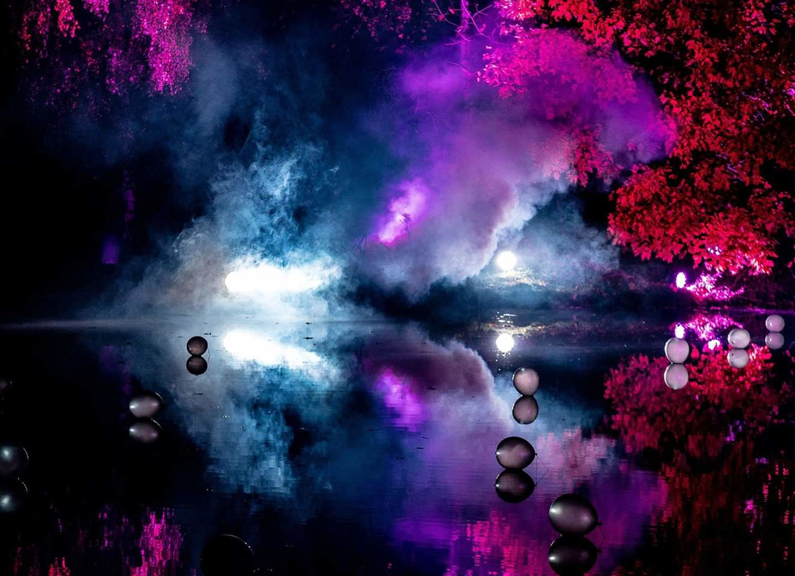 night, illuminated, smoke - physical structure, beauty in nature, outdoors, water, pink color, no people, multi colored, arts culture and entertainment, nature, motion, celebration, purple, lighting equipment, nightlife