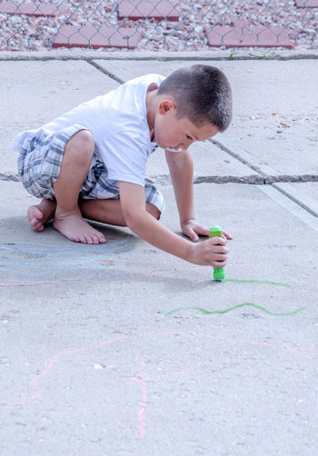 sidewalk chalk, sunshine, a smooth driveway and lots of imagination is all this little boy needsKids Summertime Active Kids Art Boys Childhood Creative Day Drawing Kids Having Fun One Person Outdoors People Playing Outdoors Real People Sidewalk Chalk