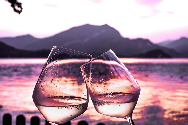 Close-up of drink in lake against sky during sunset