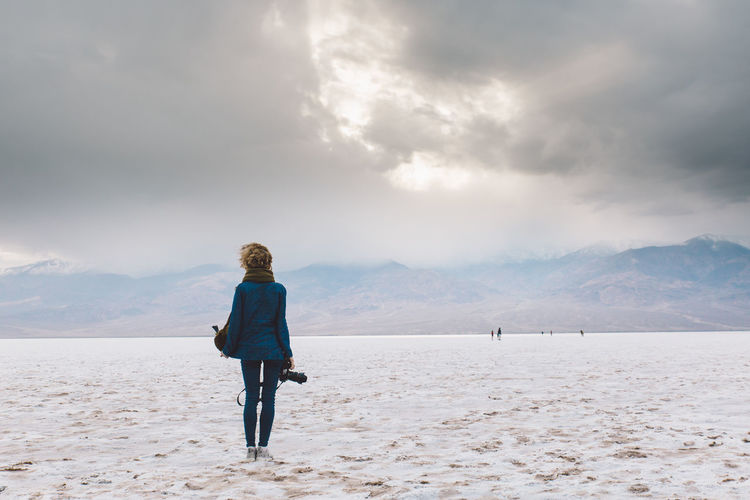 Rear view of woman holding camera standing on snow covered land
