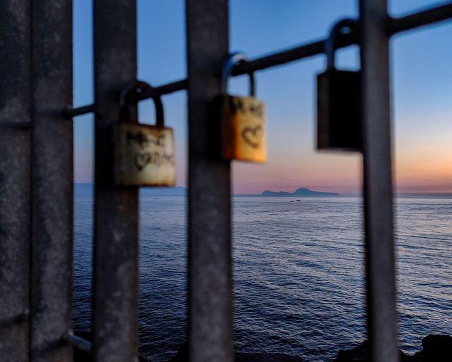 Close-up of padlocks on railing against sea