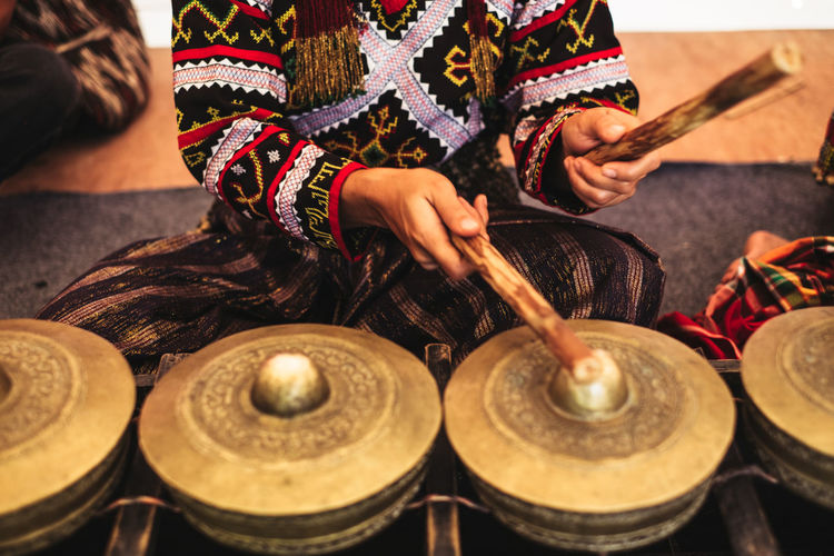 Midsection of woman playing traditional musical equipment