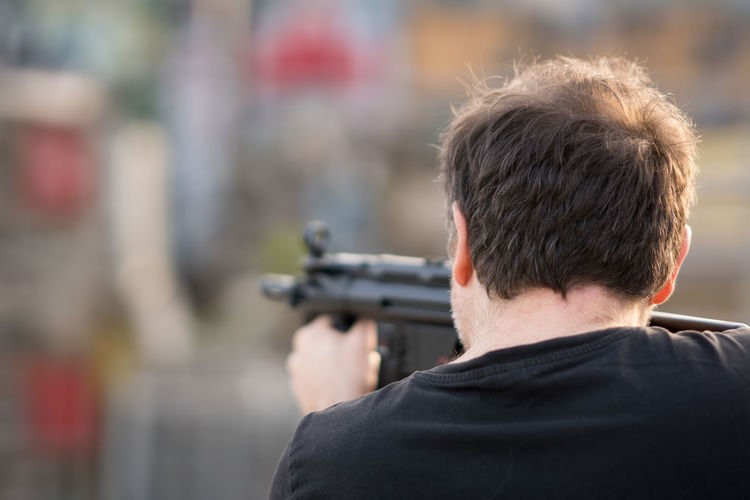 Rear view of man shooting gun outdoors