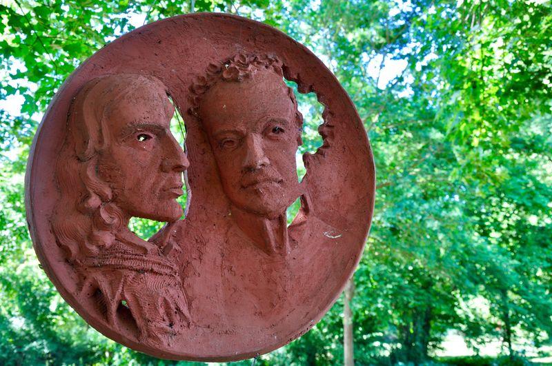 V. Chamisso und F. de la Motte Fouqué Facemasks Circle Frame Hanging Terracotta Colour Terracotta Relief Tree Art And Craft Representation Human Representation Creativity Sculpture Park - Man Made Space Close-up Outdoors
