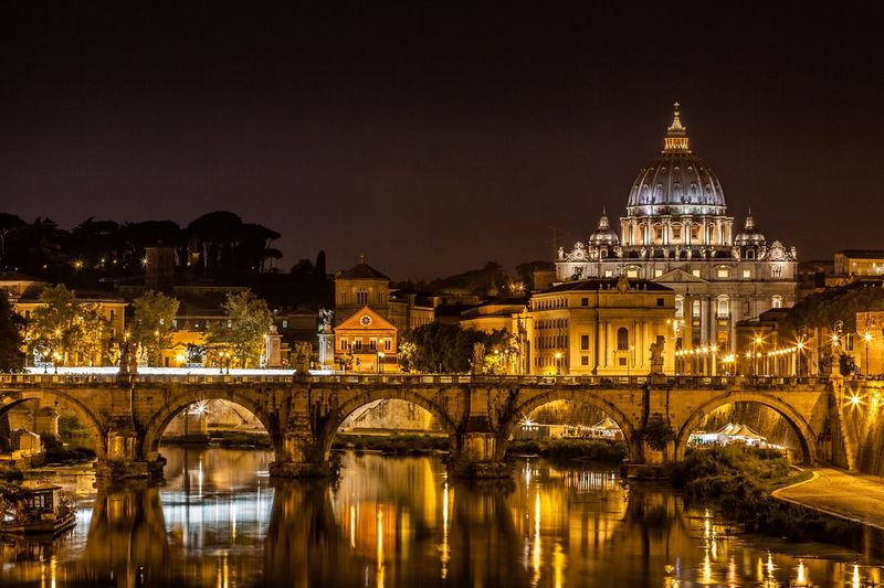 Illuminated ponte sant angelo bridge over tiber river against st peter basilica