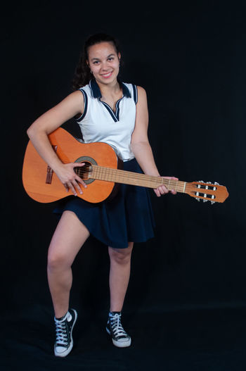 Portrait of smiling young woman playing guitar