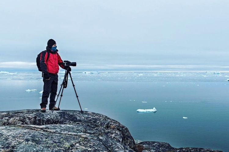 SCENIC VIEW OF Man On Rock Formation Photographing Frozen SEA