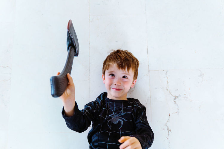 Portrait of boy standing against wall