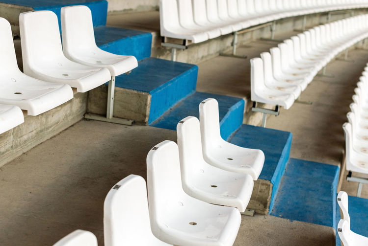 White stadium seats with stairs. Soccer, football or baseball stadium tribune without fans. End of the game. Stadium Seat Chair Soccer Football Tribune Plastic Empty Dirty Public Sector Row Nobody Stage Sport Game Section Arena Audience Bench Background Theater Color LINE Objects Bleachers Place Event Seating Outdoors Horizontal STAND Number Perspective Field Texture Stairs Baseball Concert Group Concept Pattern Architecture Multiple Entertainment France Fan Club Scored White