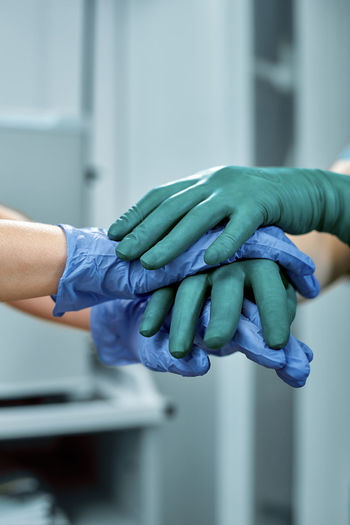 Cropped image of doctors stacking hands at hospital