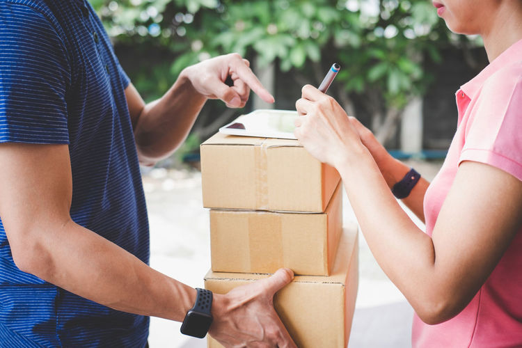 Midsection of delivery man giving cardboard boxes to woman