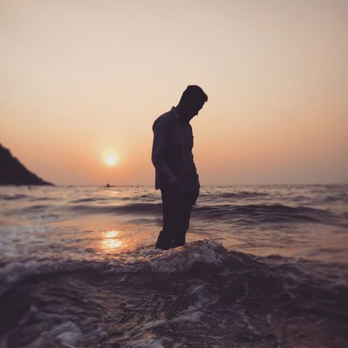 Man standing in sea during sunset