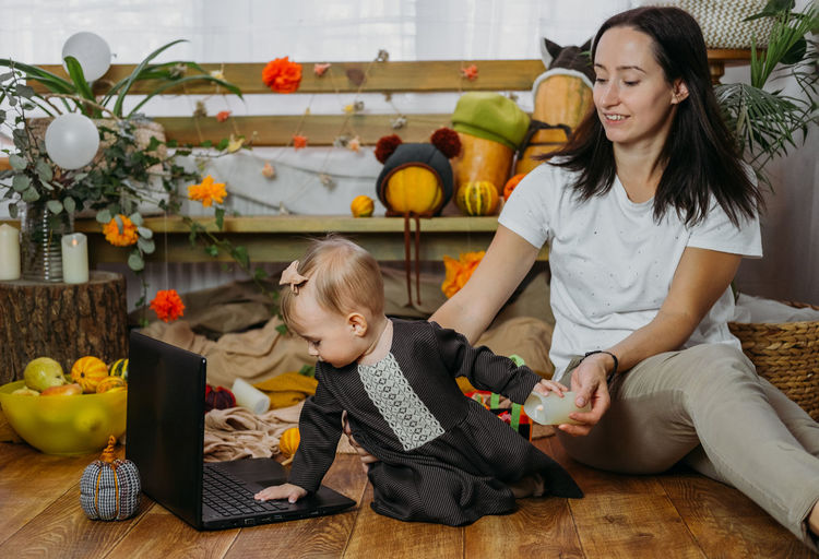 Cheerful mother with daughter looking at laptop at home