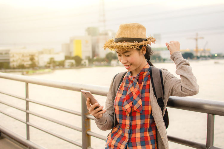 Young woman using mobile phone while standing on bridge