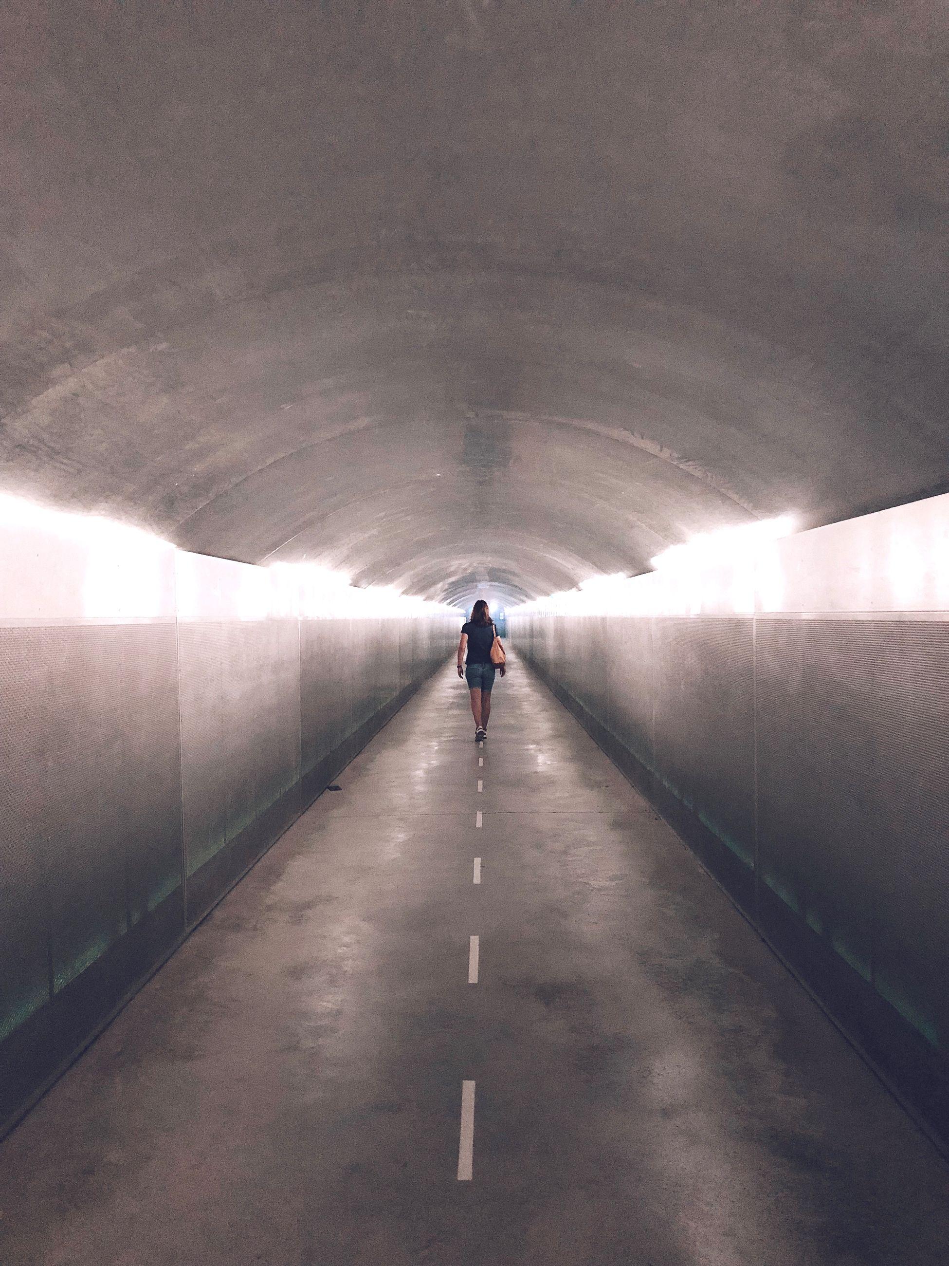 FULL LENGTH REAR VIEW OF MAN WALKING IN TUNNEL