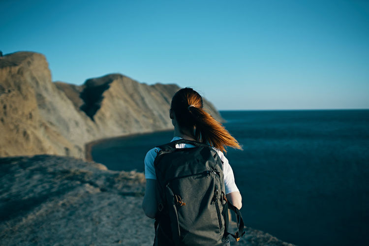 Rear view of woman standing against sea against clear blue sky