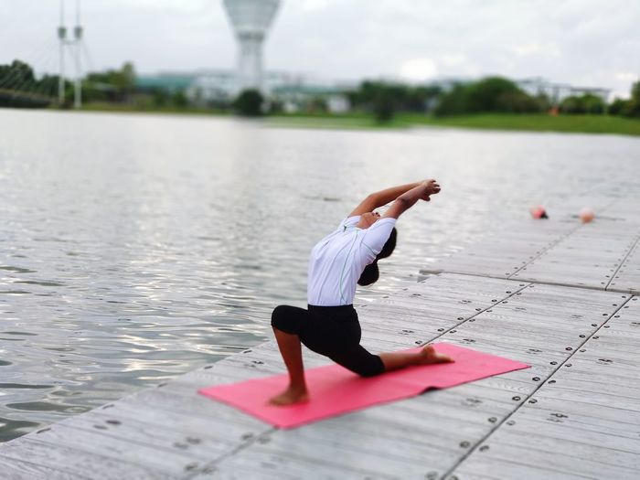 Woman Practicing Yoga On Pier In Lake