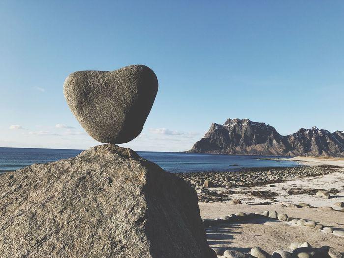 Heart shaped rock on beach against clear sky