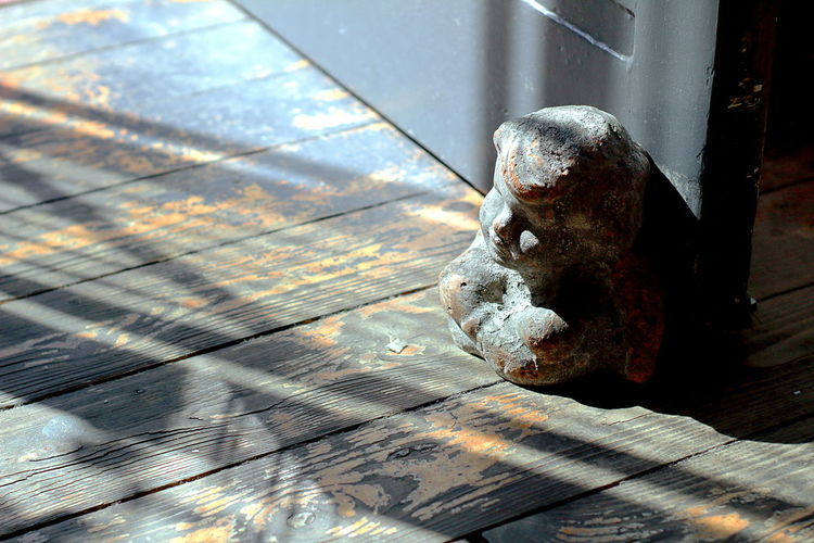 Shadow And Light Cherub Close-up Day Design Element Deterioration Door Doorstop Focus On Foreground High Angle View Interiors Design Interiorstyling Light And Shadow No People Old Sculpture Security Sunlight Weathered Wood - Material