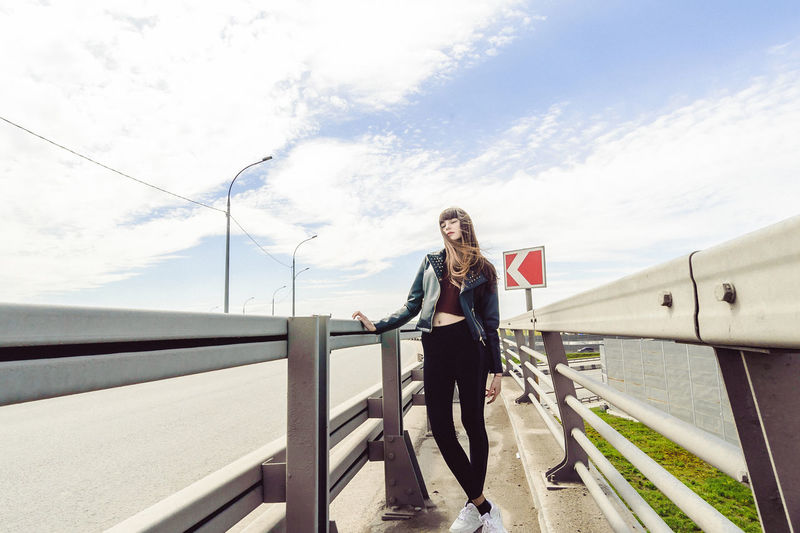 Adult Beautiful Woman Casual Clothing Cloud - Sky Day Front View Full Length Hair Hairstyle Leisure Activity Lifestyles Nature One Person Outdoors Railing Real People Sky Standing Transportation Wind Women Young Adult Young Women