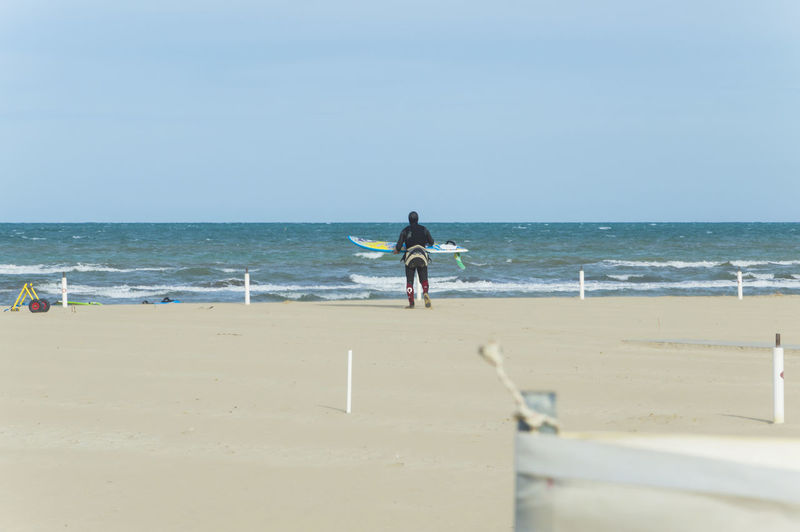 Rear View Of Man With Surfboard Walking At Beach