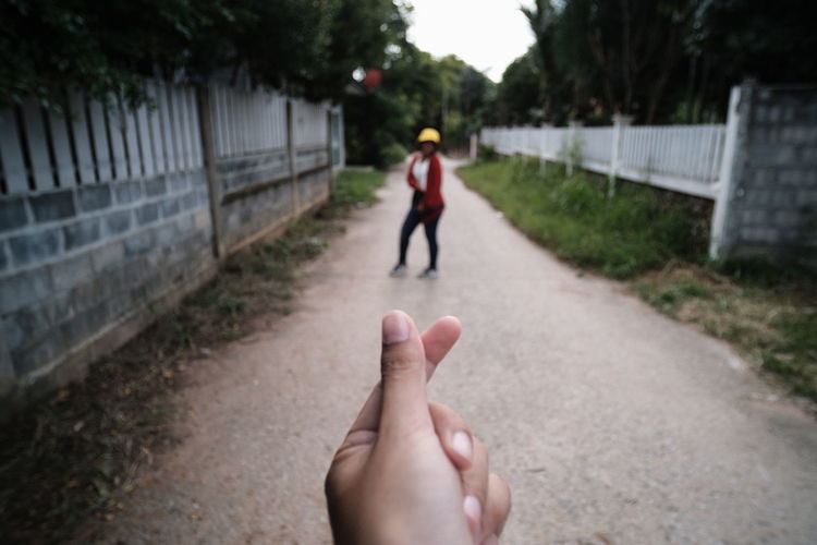 Rear view of man hand on footpath