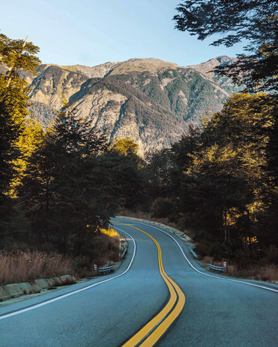 Country road amidst trees and mountains against sky