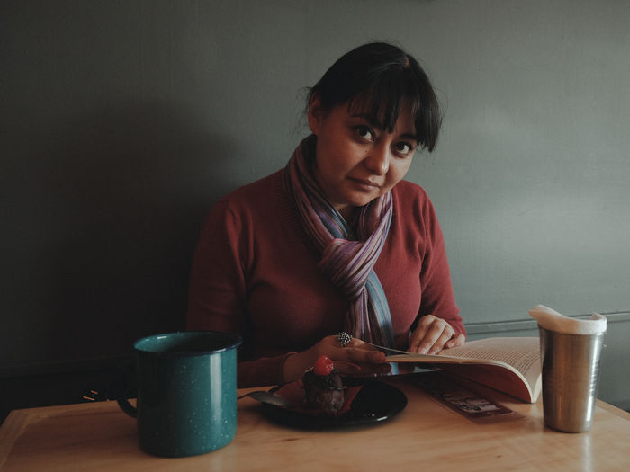 Portrait Of Woman Holding Book While Sitting At Cafe