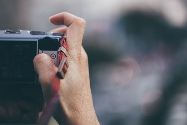 Cropped hand of person photographing with camera outdoors