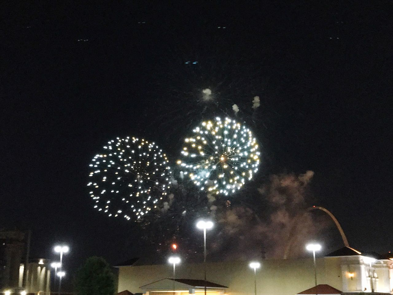 LOW ANGLE VIEW OF FIREWORK DISPLAY OVER STREET