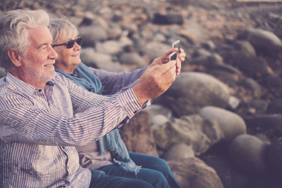 senior couple white and grey hair, mobile technology, front of ocean Adult Casual Clothing Eyeglasses  Friendship Grey Hair Lifestyles Love ♥ Men Mobile Nature Outdoors Real People Relaxing Moments Retirement Rock Beach Sea Selfie Senior Adult Senior Couple Sunset Togetherness Two People Volunteer