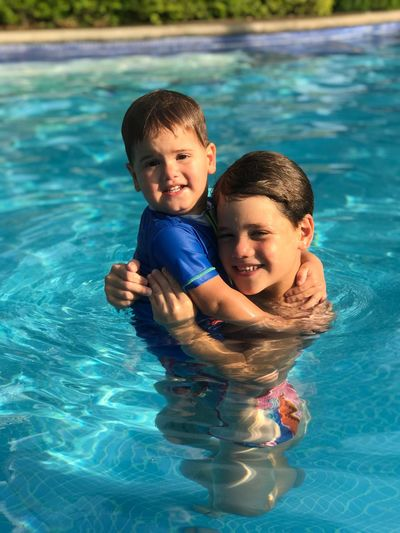 High angle portrait of brothers enjoying in swimming pool