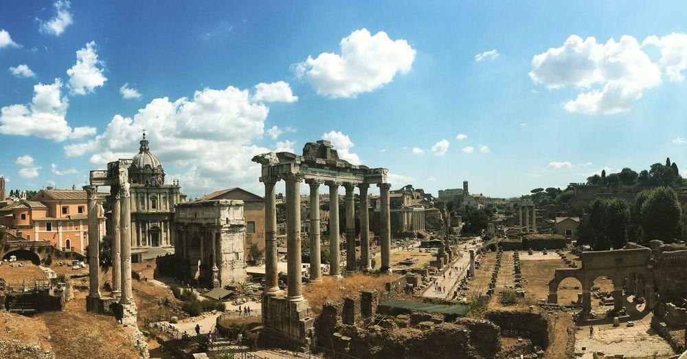 Coliseum by buildings against cloudy sky