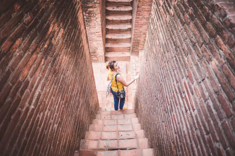 High angle view of woman standing on steps of historical building